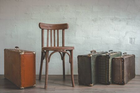 wooden chair: Old suitcase and a wooden chair standing in an empty room Stock Photo