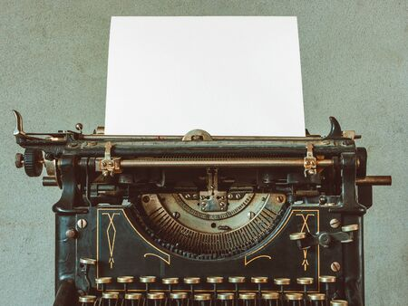 hoja en blanco: The old typewriter with a blank sheet of paper.Close-up