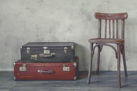 silla de madera: Maleta vieja y una silla de madera de pie en una habitación vacía