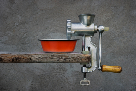enameled: Old meat grinder and red enameled bowl on a background a concrete wall