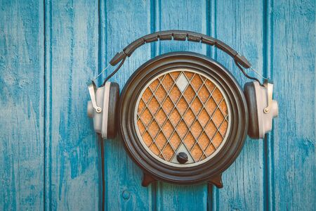 black rapper: Old radio and headphones hanging on a blue wooden wall