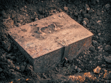 Old metal chest with the treasure found in the ground Stockfoto