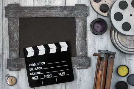 Clapperboard, reels of film, a tripod is the lens on the table Stock Photo