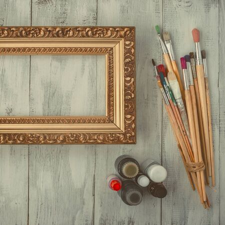 Brushes, paint and old with gold frame for a picture on the table