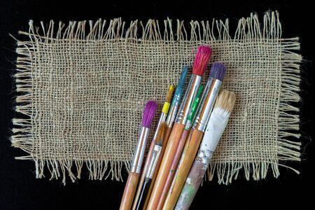 Brushes for painting artist and a piece of linen cloth lying on a black background Stock Photo