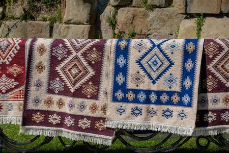 Georgische Teppiche handgemacht mit den nationalen Verzierungen, die an einem Metallzaun hängen Standard-Bild - 81192720