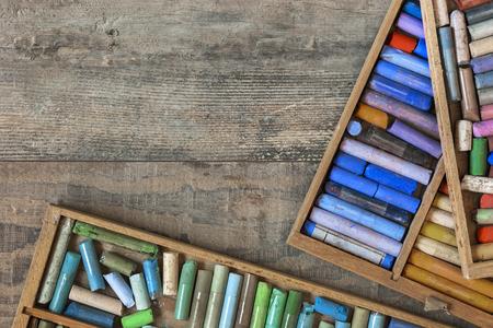 Oude houten dozen met gekleurde pastelkrijt liggen op een getextureerde houten tafel