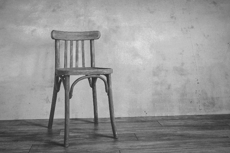 An Old Wooden Chair Stands In An Empty Room On The Background Of A Concrete  Wall