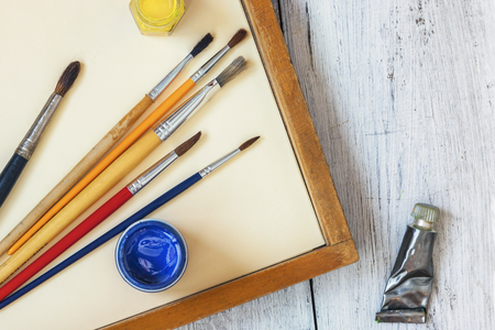 Brushes and colored paints in cans stand in a wooden tablet on a white sheet background