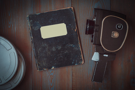 An old movie camera, a box of films and a notebook for notes lie on the table Stok Fotoğraf
