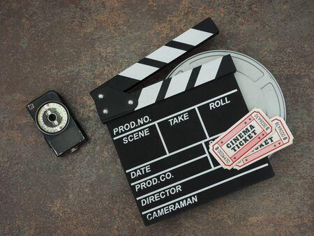 Clapperboard, Kinokarten und der Belichtungsmesser liegen auf dem Tisch. Von oben betrachten.