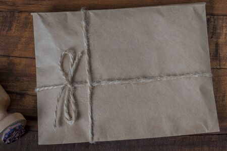 A paper envelope tied with linen rope and an ink seal lie on a wooden table