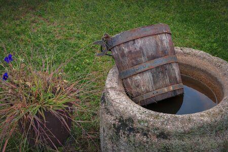 Un vecchio secchio di legno giace su un pozzo di cemento con acqua