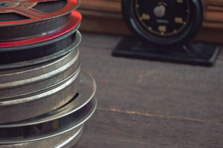 Old metal reels with film strip stand on a wooden table next to a timer
