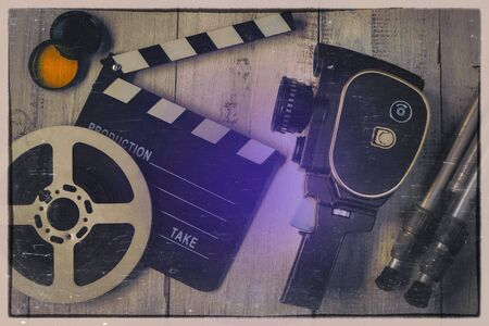 Old movie camera, clapperboard, film on a reel, color filters and a tripod shot from above. Cinema equipment. Stylized photo.
