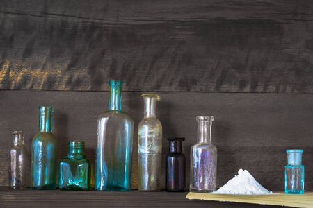 Old pharmacy bottles stand on a wooden shelf near a slide with white medicinal powder