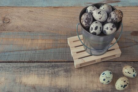 Tin bucket with fresh quail eggs stands on a wooden rustic table