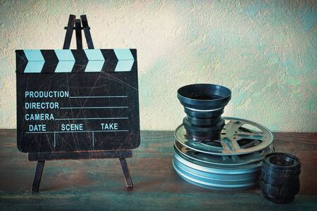 Movies, lenses and clapperboard on a wooden table. Stylized photo.