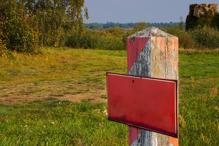 Old wooden border post with red prohibition sign Stockfoto