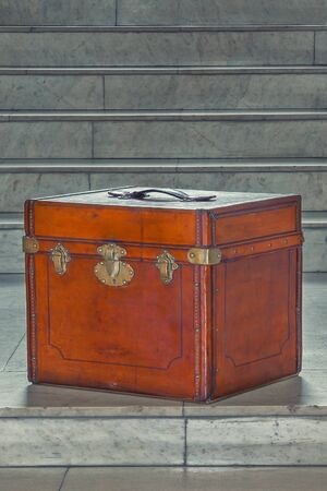 An antique red leather travel chest stands on the steps of a marble staircase.