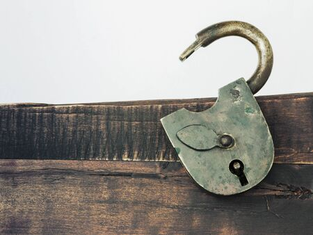 An old padlock with an open arc is removed on the background of a wooden panel