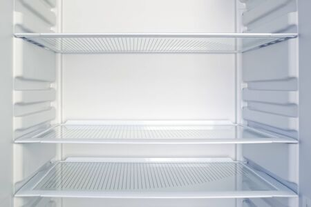 Empty open modern fridge with clean glass shelves. Weight loss, diet and hunger concept