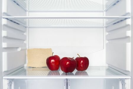 Three red apples on the shelf of an empty fridge. A piece of paper with free space for text. The concept of weight loss, hunger