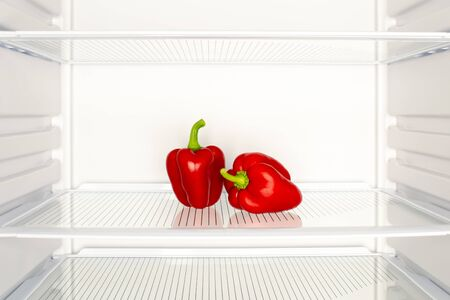 Two red peppers in an empty fridge. Diet, vegetarianism, weight loss concept Stock fotó