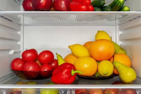 Refrigerator filled with useful products. Vegetables and fruits. Cucumbers, tomatoes and peppers, apples, pears, lemons, oranges and grapefruits. Diet, vegetarianism, weight loss concept