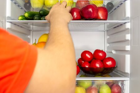 Fridge is filled with useful products. Vegetables and fruits. A mans hand takes food from the refrigerator. Diet, vegetarianism, weight loss concept