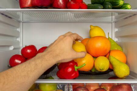 The refrigerator is filled with useful products. Vegetables and fruits. A mans hand takes a lemon from the fridge. Diet, vegetarianism, weight loss concept
