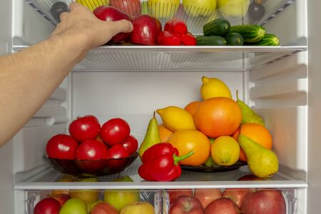Fridge is filled with useful products. Vegetables and fruits. A mans hand takes a red Apple from the refrigerator. Diet, vegetarianism, weight loss concept
