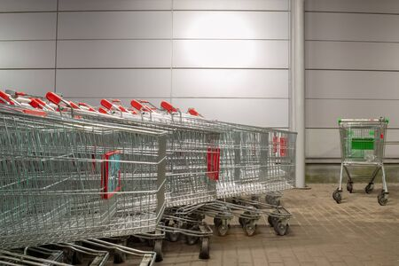 A cluster of identical shopping carts. Aside from them is a single cart of a different color. The concept of individuality, leadership, independence.