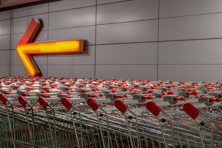 Une rangée de chariots de supermarché dans la rue, à côté du magasin. Au fond, le mur sur lequel est accrochée une pancarte en forme de gros pointeur Banque d'images