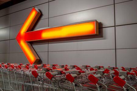 Eine Reihe von Einkaufswagen auf der Straße, neben dem Laden. Im Hintergrund befindet sich eine Wand, an der ein Schild in Form eines großen orange leuchtenden Zeigers angebracht ist.