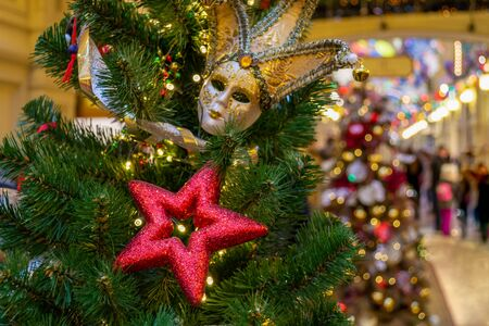 Christmas decorations. Red stars, masquerade mask, silver ribbons decorate the Xmas tree. Festive interior in the background. Indoor. Bokeh. Close-up Banque d'images