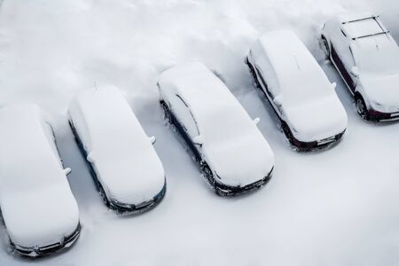Parked cars and the road are covered with smooth layer of snow. Top view, aerial photography. Winter daytime. Фото со стока