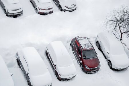 Parked cars and the road are covered with smooth layer of snow but one red car from them are cleared from snow and ice. Top view, aerial photography. Winter, daytime