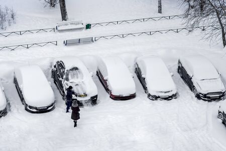 Man, using brush to remove snow from the car. The rest of the cars are covered with an even layer of snow. Top view, aerial photography. Winter daytime.