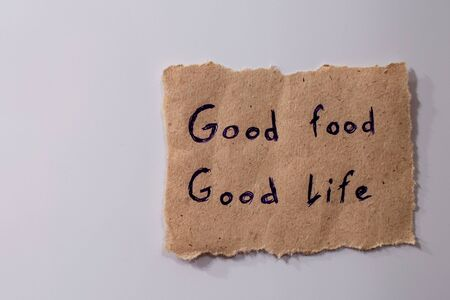 Paper note labeled with sign good food - good life attached to the refrigerator door. Close-up. Diet concept