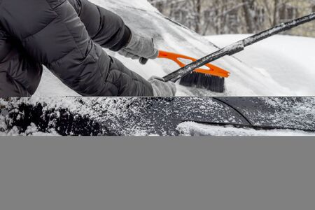 Man lifted the windshield wiper to clear the snow from the windshield, using Car Snow Brush for this. Person in a black jacket and gray gloves. Close-up. Winter, daytime.