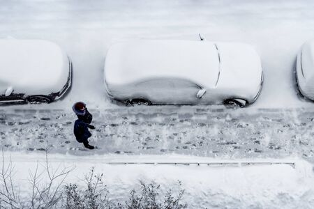 Parked cars and the road are covered with layer of snow. On the sidewalk are two people, a man and a woman. Top view, aerial photography. Winter daytime.