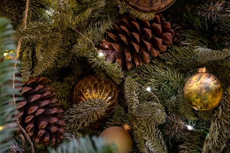Christmas decorations. Composition of Xmas toys, cones and branches of spruce. Glowing garland. Close-up. Фото со стока