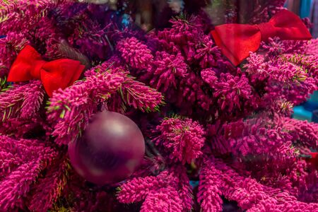 Christmas decorations. Purple branches of Xmas tree, decorated with red bows and purple Christmas toys. Close-up