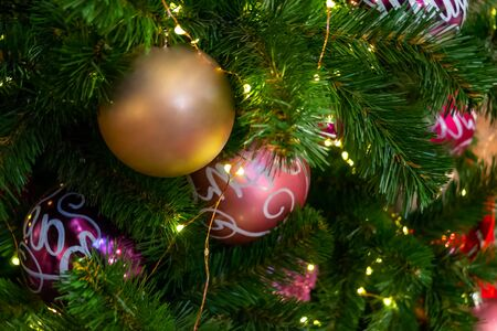 Christmas toys, balls of pink, purple and gold colors, shining garland on the Xmas tree. Close up