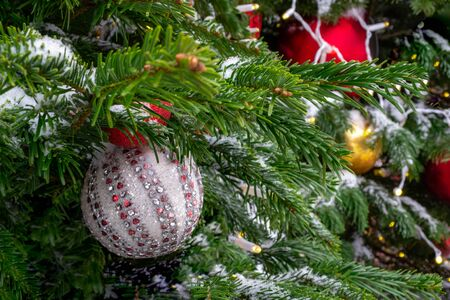 Christmas decorations. Real spruce covered with snow. Christmas tree toy, a ball of white and silver color with a heart on top and a shiny garland hanging on a branch. Close-up. Macro. Xmas Banque d'images