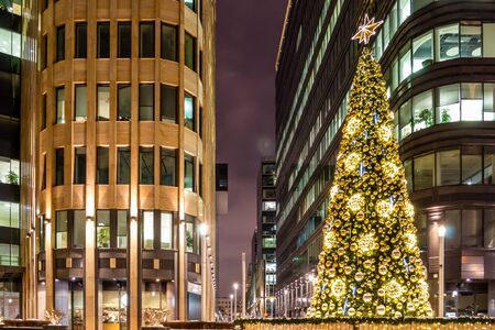 Christmas tree is decorated with lights, balls, toys and garlands, and star of gold color at the top. Facades of modern buildings in the background. Winter evening. Banque d'images