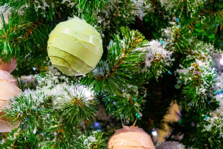 Christmas decorations. Custom Christmas design. Christmas toy, a ball-a stylized ball of ice cream, hanging on a branch of a fir tree. Close-up. Xmas