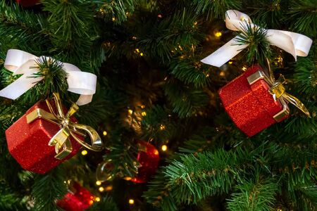 Toy gifts boxes with white bows, a shining garland hang on the branches of a Christmas tree. close-up