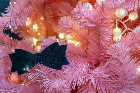 Xmas decorations. Pink branches of the Christmas tree. Decorated with garland and toy in the form of bow-tie . Custom design. Close-up Фото со стока